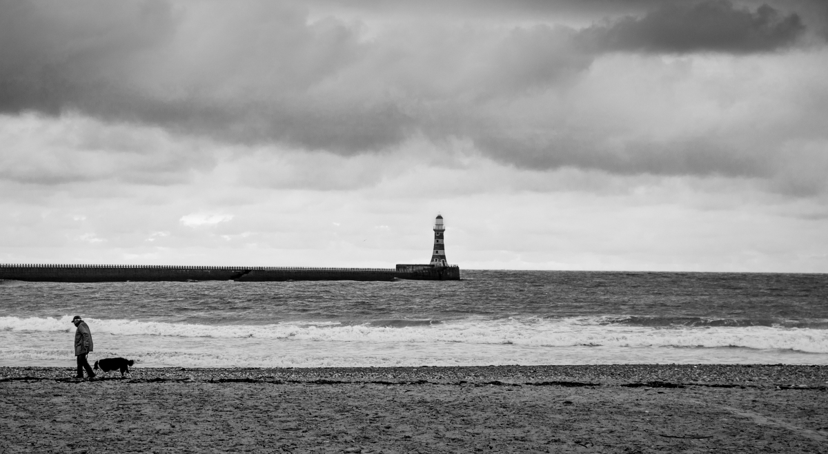 seaham beach showing a solitary man walking a dog with lighthouse in the background
