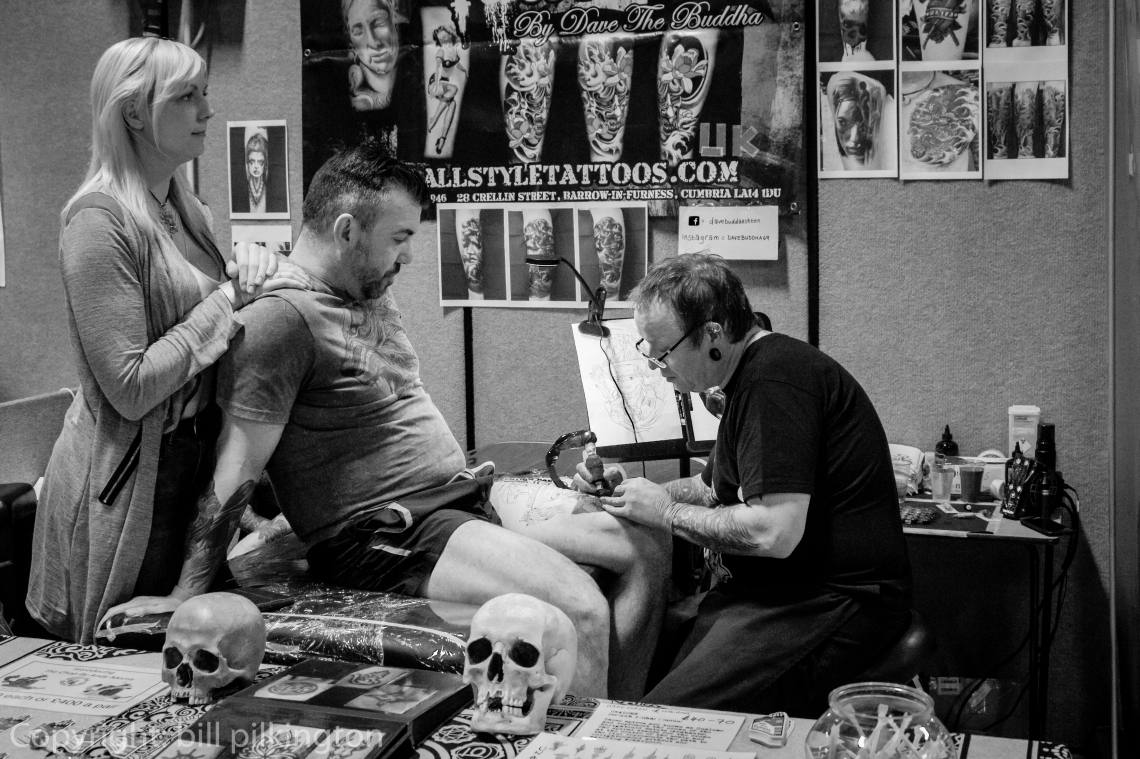 image of a guy having his leg tattoed