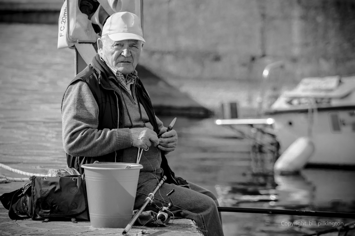 a man sitting with legs dangling over a harbour wall with a fishing rod on his knee