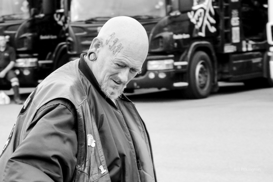 close up photo of a biker with bald head and very large ear piercing