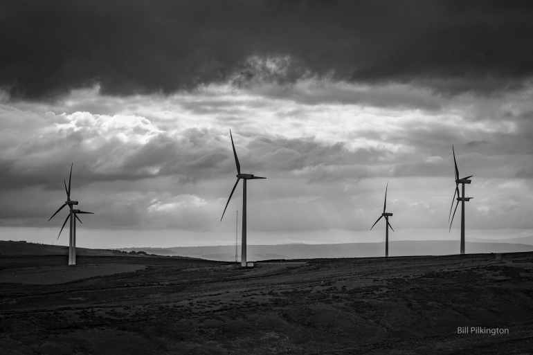 black and white photo of wind turbines silhouetted against a stormy sky