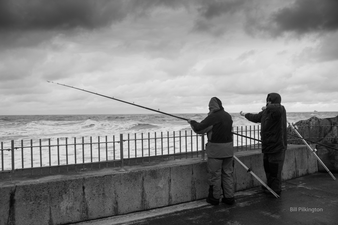 two guys fishing from a harbour wall on a stormy day